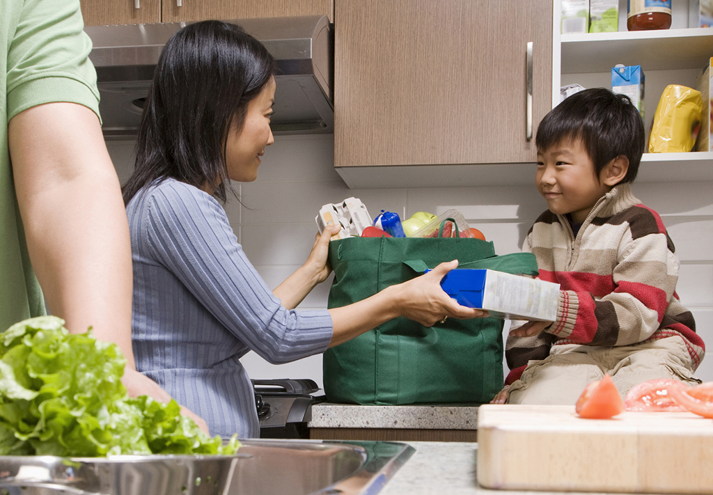 Photo of a family unpacking groceries in the kitchen